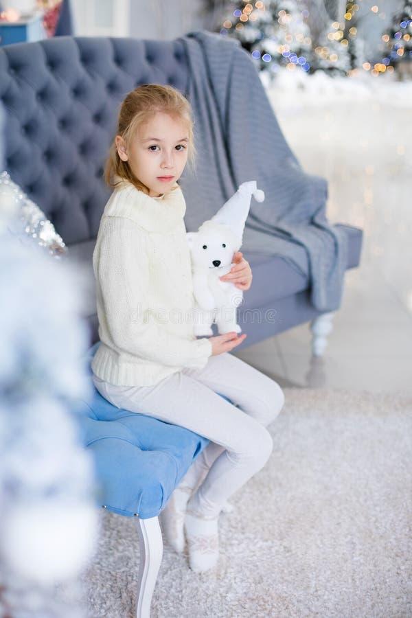 Веселое рождество и С Новым Годом!! Очаровывая маленькая белокурая девушка в белом теплом свитере с медведем игрушки сидя на голу стоковая фотография rf