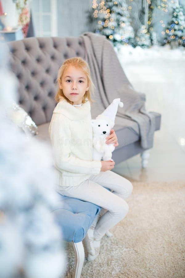 Веселое рождество и С Новым Годом!! Очаровывая маленькая белокурая девушка в белом теплом свитере с медведем игрушки сидя на голу стоковое фото
