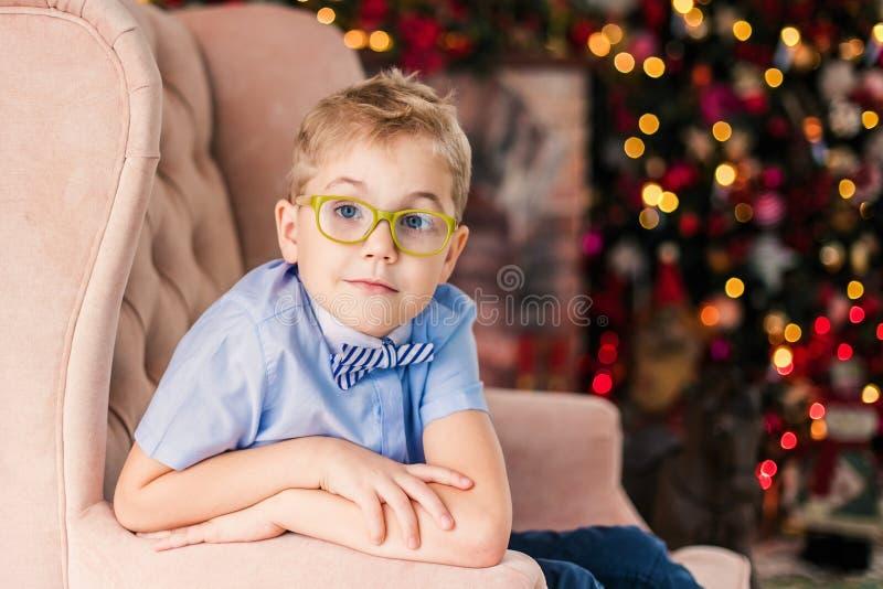 Веселое рождество и С Новым Годом!! Очаровывая маленький белокурый мальчик в голубой рубашке с большими стеклами сидя на arnchair стоковые изображения