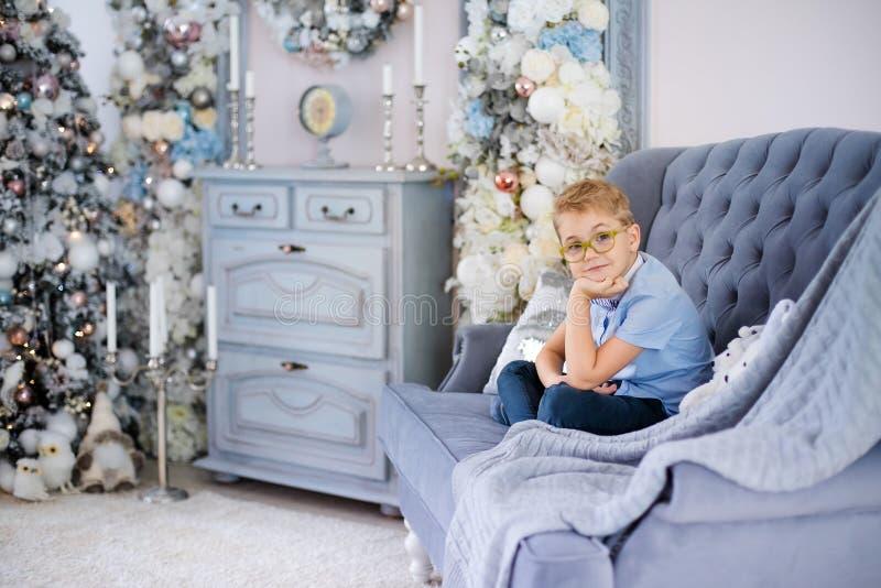 Веселое рождество и С Новым Годом!! Очаровывая маленький белокурый мальчик в голубой рубашке с большими стеклами сидя на софе око стоковые фотографии rf