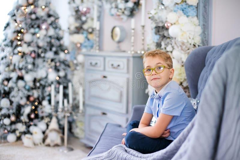 Веселое рождество и С Новым Годом!! Очаровывая маленький белокурый мальчик в голубой рубашке с большими стеклами сидя на софе око стоковое фото rf