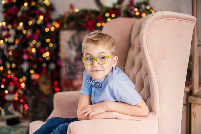 Веселое рождество и С Новым Годом!! Очаровывая маленький белокурый мальчик в голубой рубашке с большими стеклами сидя на arnchair стоковое фото