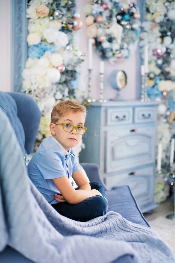 Веселое рождество и С Новым Годом!! Очаровывая маленький белокурый мальчик в голубой рубашке с большими стеклами сидя на софе око стоковое фото