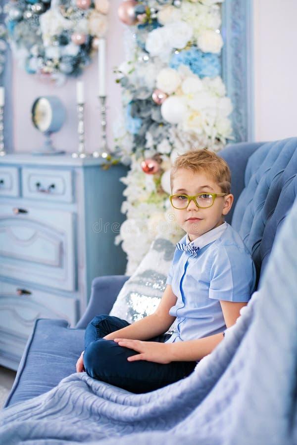 Веселое рождество и С Новым Годом!! Очаровывая маленький белокурый мальчик в голубой рубашке с большими стеклами сидя на софе око стоковая фотография