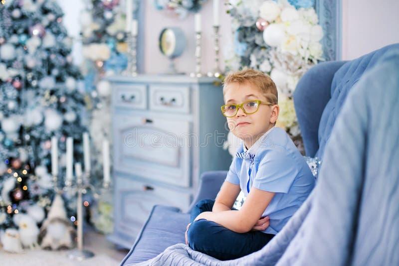 Веселое рождество и С Новым Годом!! Очаровывая маленький белокурый мальчик в голубой рубашке с большими стеклами сидя на софе око стоковые изображения