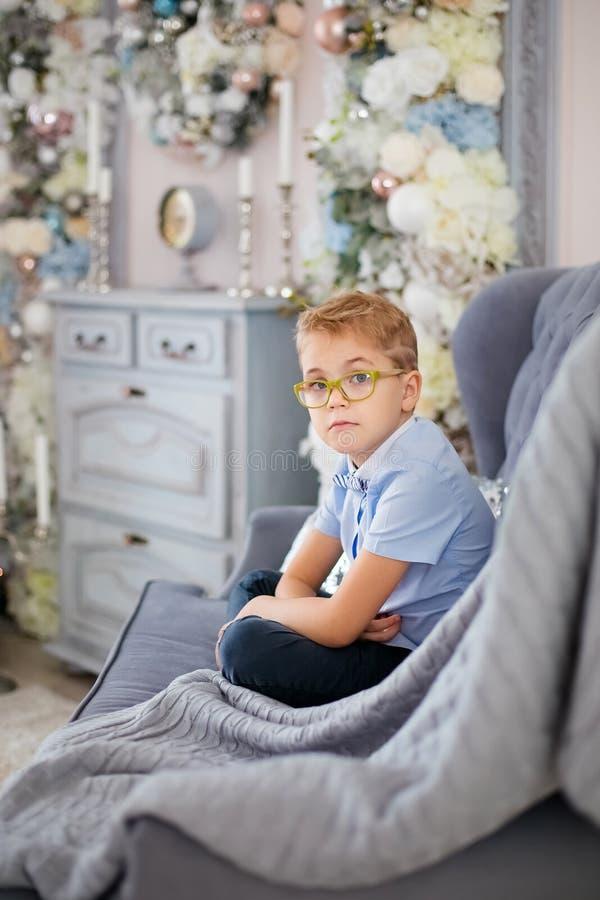 Веселое рождество и С Новым Годом!! Очаровывая маленький белокурый мальчик в голубой рубашке с большими стеклами сидя на софе око стоковое изображение