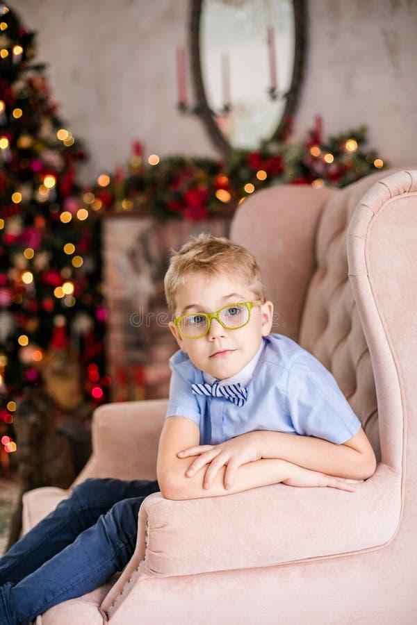 Веселое рождество и С Новым Годом!! Очаровывая маленький белокурый мальчик в голубой рубашке с большими стеклами сидя на arnchair стоковые фотографии rf