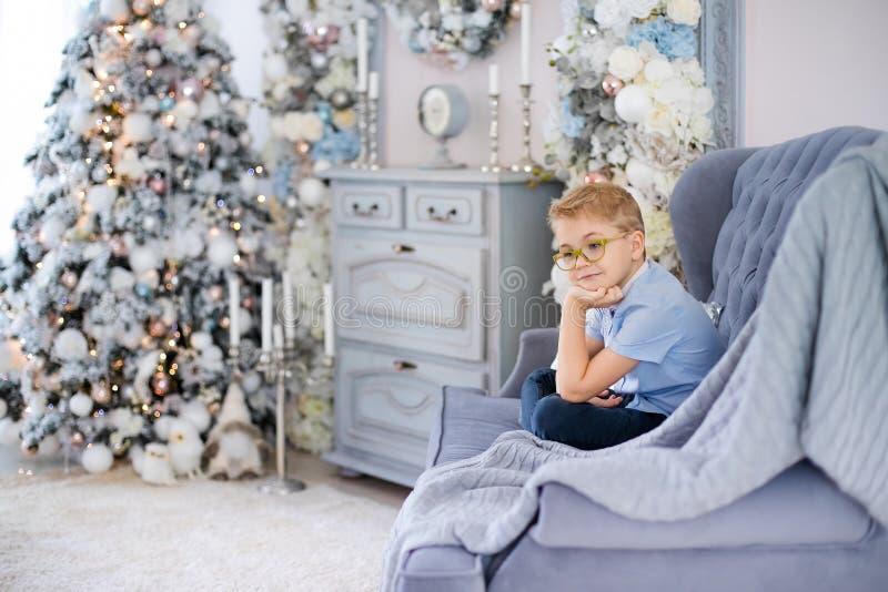 Веселое рождество и С Новым Годом!! Очаровывая маленький белокурый мальчик в голубой рубашке с большими стеклами сидя на софе око стоковая фотография rf