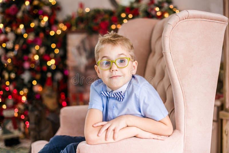Веселое рождество и С Новым Годом!! Очаровывая маленький белокурый мальчик в голубой рубашке с большими стеклами сидя на arnchair стоковые изображения rf