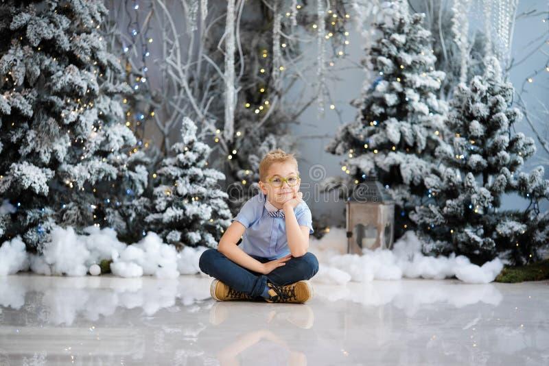 Веселое рождество и С Новым Годом!! Очаровывая мальчик сидит дома, снежной дерево украшенное зимой на предпосылке Новый Год стоковая фотография