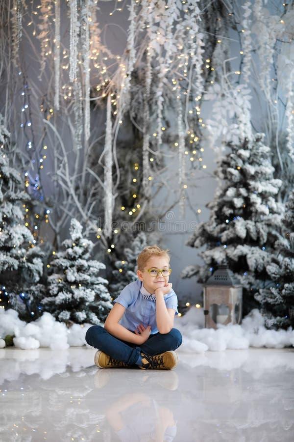 Веселое рождество и С Новым Годом!! Очаровывая мальчик сидит дома, снежной дерево украшенное зимой на предпосылке Новый Год стоковое изображение