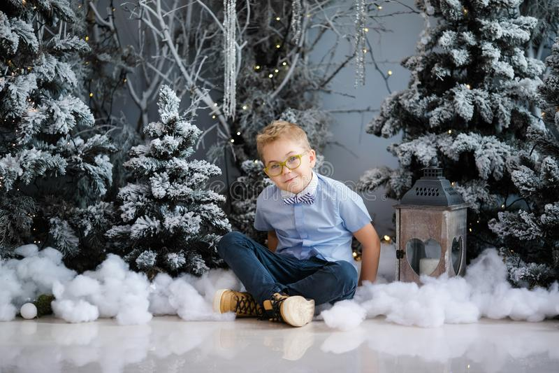 Веселое рождество и С Новым Годом!! Очаровывая мальчик сидит дома, снежной дерево украшенное зимой на предпосылке Новый Год стоковое фото rf