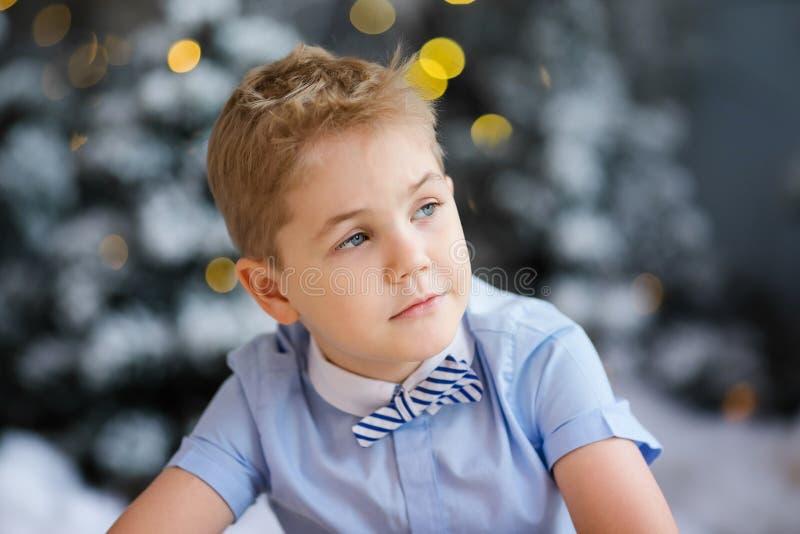 Веселое рождество и С Новым Годом!! Очаровывая мальчик сидит дома, снежной дерево украшенное зимой на предпосылке Новый Год стоковые изображения rf
