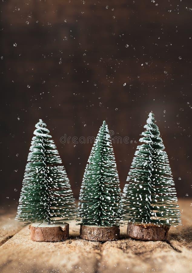 Веселое рождество с деревом и снегом xmas падая на таблицу grunge деревянную и темную коричневую деревянную стену поздравительная стоковые фотографии rf