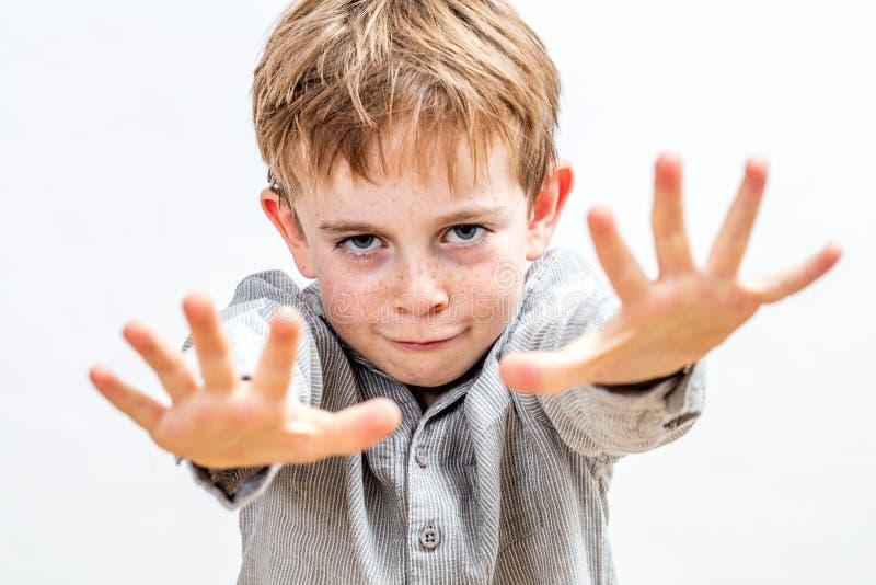 Веселый ребенок, притворяющийся магом с решительным жестом руки стоковые изображения
