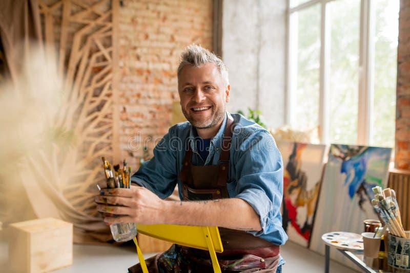 Веселый художник в рабочем одеянии сидит на стуле перед камерой стоковая фотография