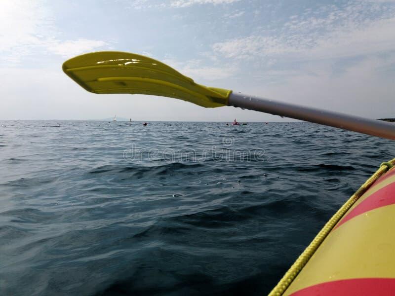 Весельная лодка и желтые весло или затвор над поверхностью моря и взглядом к горизонту стоковые фотографии rf