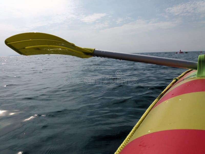 Весельная лодка и желтые весло или затвор над поверхностью моря и взглядом к горизонту стоковые изображения rf
