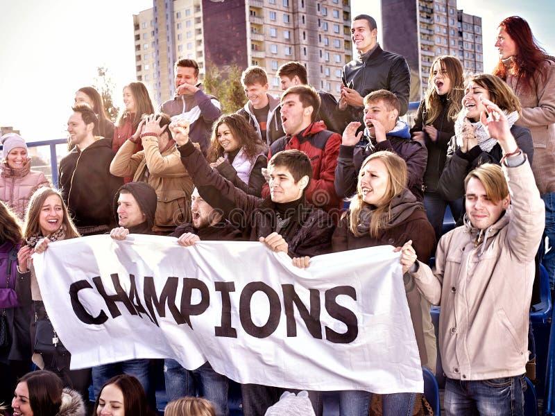Веселя вентиляторы в стадионе держа знамя чемпиона стоковые изображения
