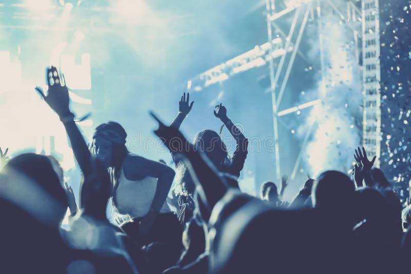 веселя толпа с поднятыми руками на концерте - музыкальном фестивале стоковое фото