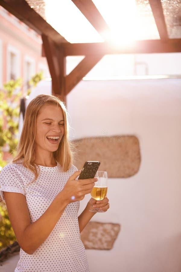 Весело смеяться над белокурый с мобильным телефоном и пивом стоковые изображения rf