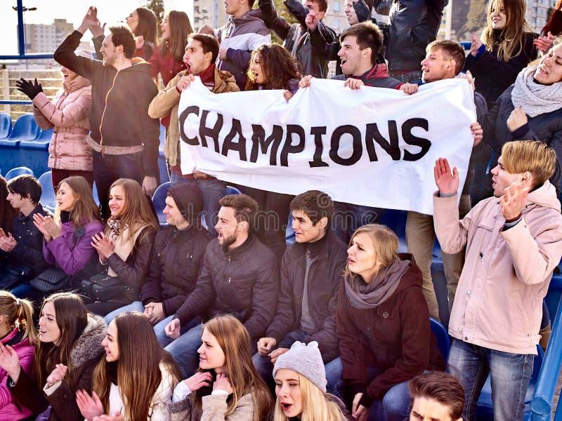 Веселя вентиляторы в стадионе держа знамя чемпиона стоковая фотография
