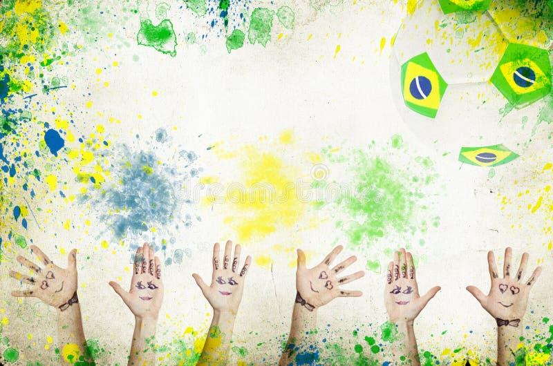 Веселя руки, футбольный мяч и цвета Бразилии стоковое фото