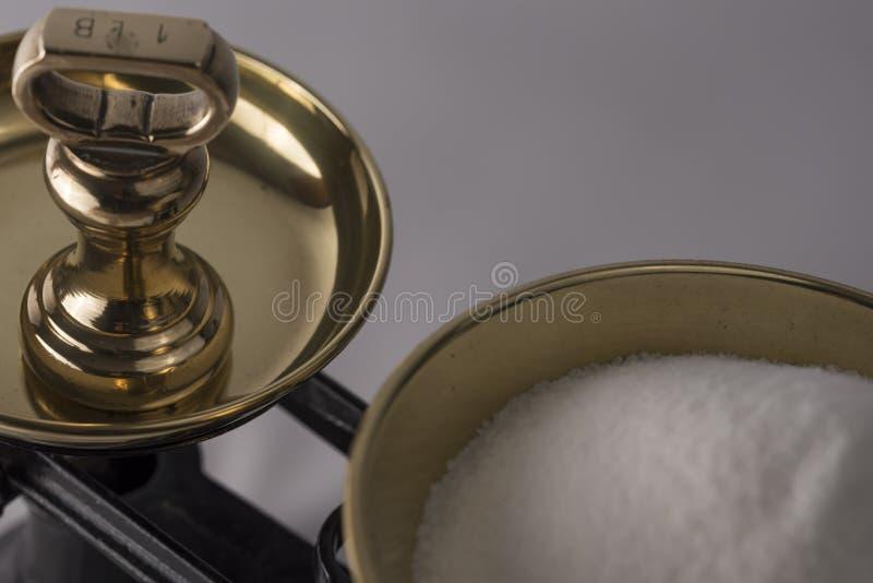 Весить сахар на масштабах баланса стоковое фото