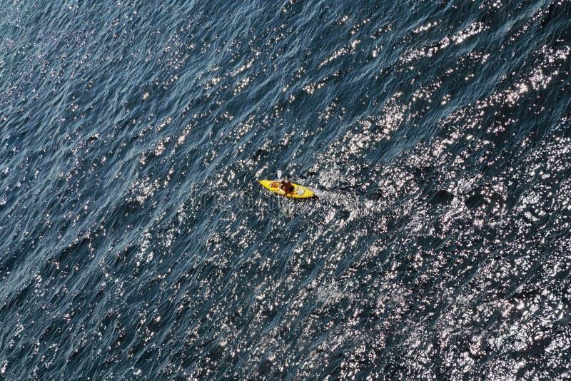 Весло рядков человека в kayak плавает на море стоковая фотография