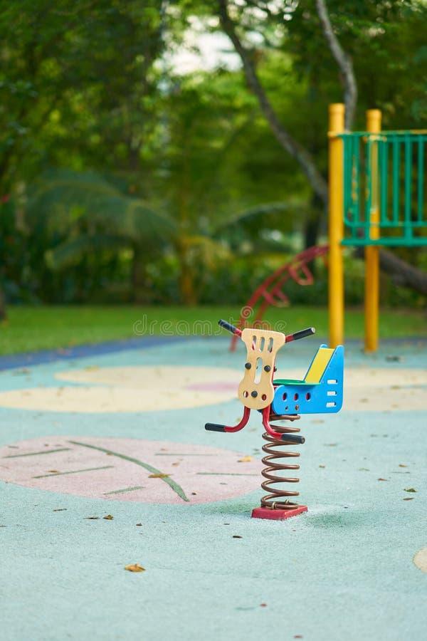 Весна видит пилу или игрушку на предпосылке спортивной площадки нерезкости стоковые фотографии rf
