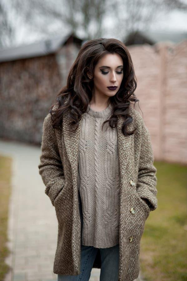 Весна в стиле страны Полнометражный портрет молодой женщины в белизне связал свитер и меховую шляпу стоя в фронте r стоковая фотография rf