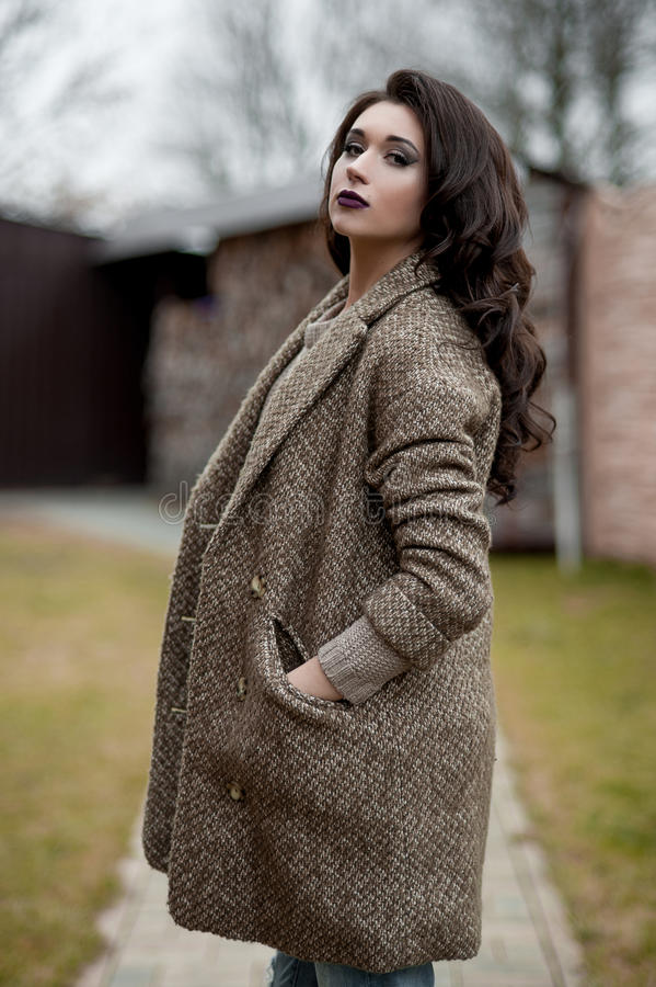 Весна в стиле страны Полнометражный портрет молодой женщины в белизне связал свитер и меховую шляпу стоя в фронте r стоковые фото
