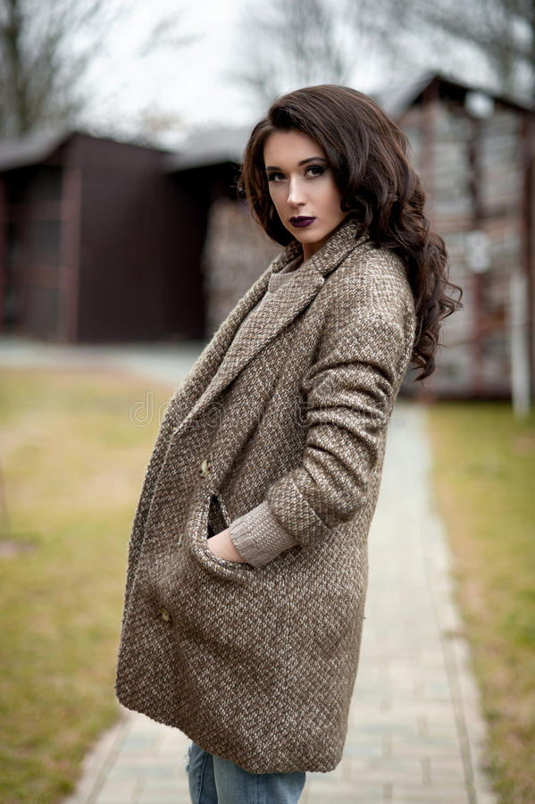 Весна в стиле страны Полнометражный портрет молодой женщины в белизне связал свитер и меховую шляпу стоя в фронте r стоковые изображения rf