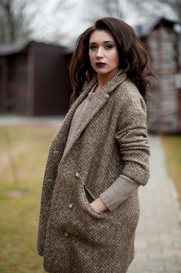 Весна в стиле страны Полнометражный портрет молодой женщины в белизне связал свитер и меховую шляпу стоя в фронте r стоковое фото