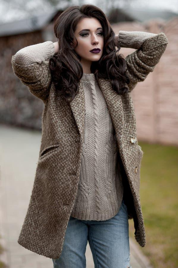 Весна в стиле страны Полнометражный портрет молодой женщины в белизне связал свитер и меховую шляпу стоя в фронте r стоковое изображение rf