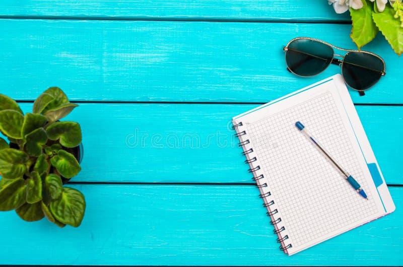 Весна, тетрадь с ручкой, цветками, стеклами на голубом деревянном bac стоковое фото rf