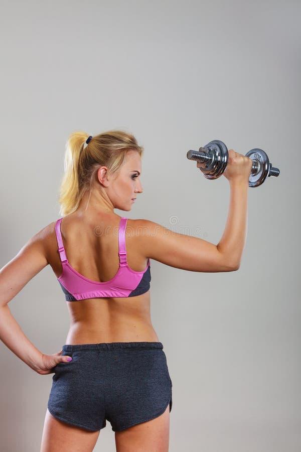 Весы гантелей подходящей женщины поднимаясь стоковое изображение