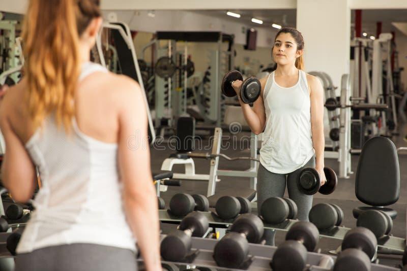 Весы милой девушки поднимаясь перед зеркалом стоковое изображение rf