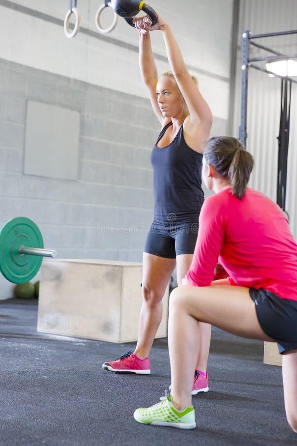 Весы kettlebells подъема женщины с личным тренером стоковые изображения rf