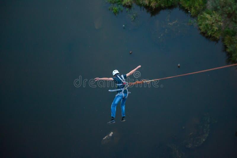 Весьма скачка от моста Человек скачет удивительно быстро в bungee скача на парк неба исследует весьма потеху Bungee ? стоковая фотография