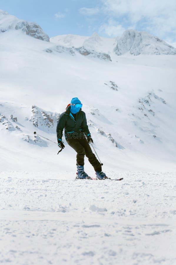 Весьма спорт зимы Лыжник человека катаясь на лыжах вниз в высоких замороженных горах стоковое фото