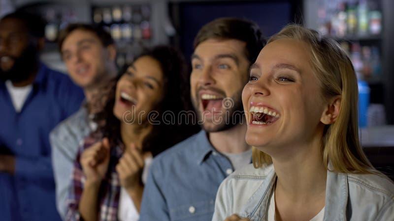 Весьма счастливая девушка наслаждаясь спичкой с друзьями, празднуя победу команды стоковые фото