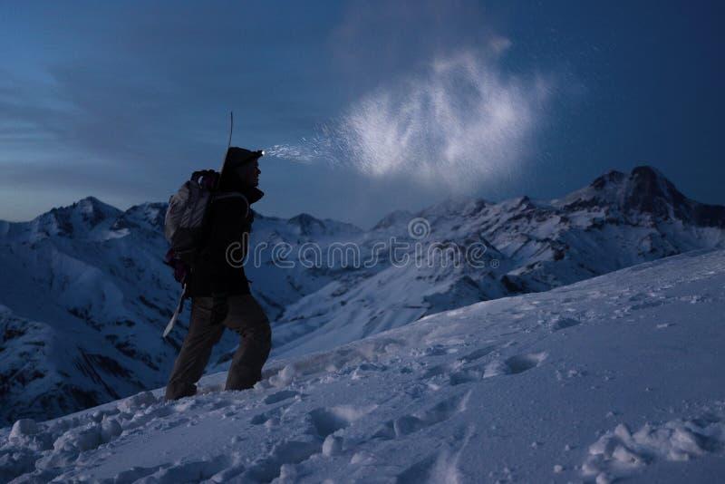 весьма туризм Храброе expeditor освещает путь с headlamp на горах зимы ночи Человек с рюкзаком совершает подъем на снежном стоковая фотография rf