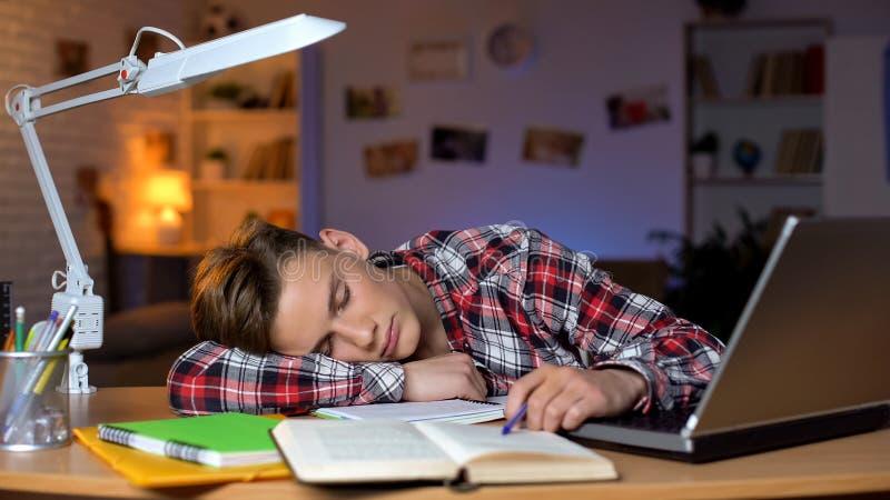 Весьма уставший студент спать таблицей на куче книг, перегруженный зрачок стоковое фото rf