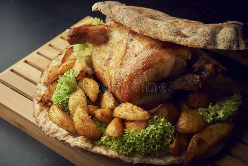 Весь испеченный цыпленок с концом-вверх картошек на таблице стоковое изображение rf
