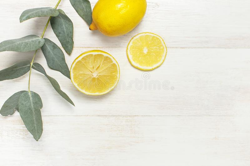Весь и отрезанный свежий лимон, листья эвкалипта на белой деревянной предпосылке Плоское положение, взгляд сверху, космос экземпл стоковые фотографии rf