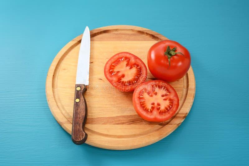 Весь и уменьшанный вдвое томат с кухонным ножом стоковые фотографии rf