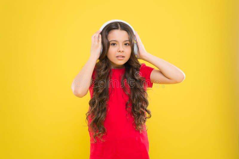 Весь музыкальный мир в ее ушах Наушники музыки ребенк слушая Развлечения и потеха Верхние песни Ребенок предназначенный для подро стоковые изображения rf