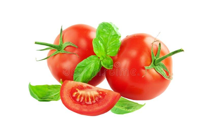 Весь томат с куском листьев томата и базилика стоковая фотография rf