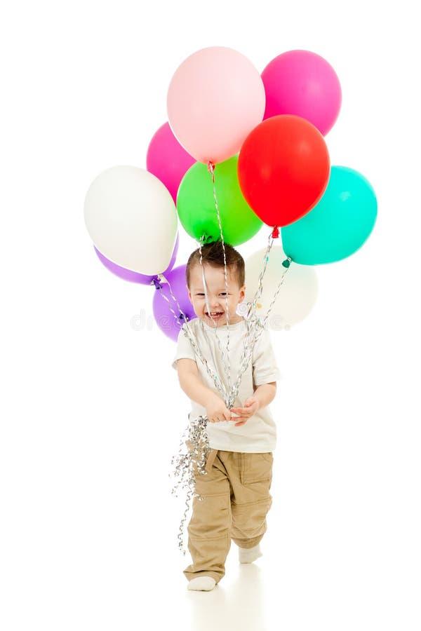 Весёлый мальчик ребенка с цветастыми воздушными шарами в руках стоковая фотография rf